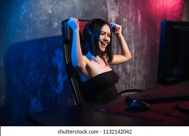 Happy cheerful cute sexy gamer girl hand gesture of win and pure emotion. Sitting at home playing video games alone on a pc computer