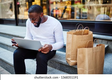 Happy cheerful dark skinned hipster guy feeling good during messaging with followers from social network while sitting with paper bags on stairs and using public internet connection on urban setting