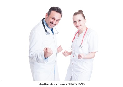 Happy and cheerful doctors act like winners and celebrate successful partnership isolated on white  studio background