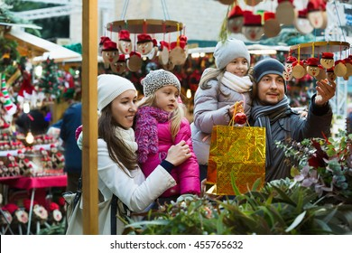 Happy cheerful family of four buying Caga Tio at Christmas market. Focus on woman and ittle girl