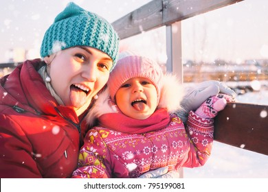 Happy cheerful family. Mother and child are walking on a frosty winter day.