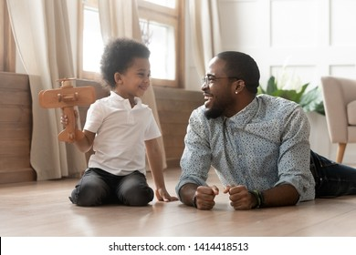 Happy cheerful family single african dad and little child boy play laugh together, cute funny small kid boy holding wooden toy plane having fun lay on floor with black father pretend fly on airplane