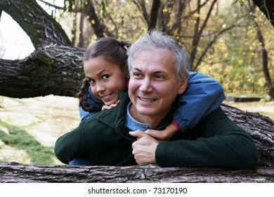 Happy cheerful father and daughter talking in autumn park