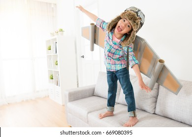 happy cheerful female children looking at camera laughing and wearing astronaut costume making fly posing standing on sofa couch enjoying play time.