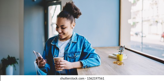 Happy cheerful female meloman feeling good during chatting with friends in group chat using smartphone application for listening music offline, smiling black hipster girl messaging via cellular