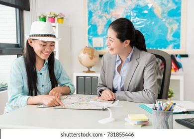 happy cheerful female traveler pointing map to ask trip question and discussing best itinerary plan with travel agent company business woman.