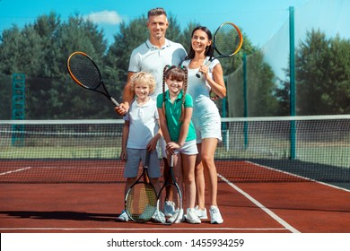 Happy and cheerful. Fit and active parents and children feeling happy and cheerful after playing tennis
