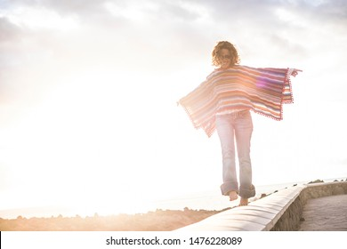 Happy cheerful free people enjoy the outdoor -woman walking in balance smiling with coloured hippy trendy style mexicn poncho - concept of leisure activity and independence
