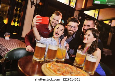 happy cheerful friends drink draft beer and clink glasses in a bar or pub