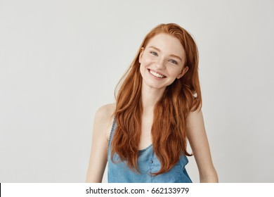 Happy cheerful ginger girl smiling looking at camera.