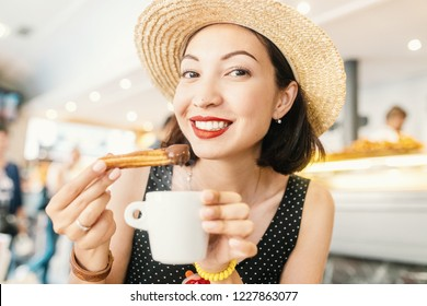 Happy Cheerful girl in hat eating traditional spanish delicious churros, a fried pastry with chocolate in cafe in spain