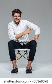 Happy cheerful handsome man pointing finger away while sitting on the chair isolated on a gray background