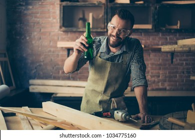 Happy cheerful joyful relaxed handsome bearded cabinet maker is celebrating the end of working day by drinking beer, he is standing near desktop