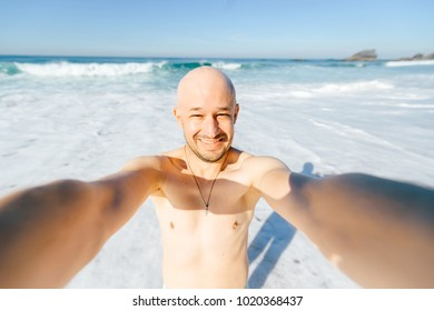 Happy cheerful joyful smiling male person making selfie in the sea under sun rays. Glad man on vacation after swimming in ocean standing on beach with waves and laughing at camera. Lens distortion.