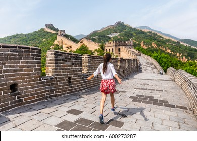 Happy cheerful joyful tourist woman at Great Wall of China having fun on travel smiling laughing and dancing during vacation trip in Asia. Girl visiting and sightseeing Chinese destination in Badaling