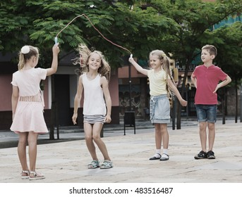 Happy cheerful kids in school age playing together with jumping rope outdoors