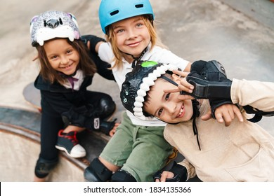 Happy cheerful kids with skateboards at the ramp, having fun