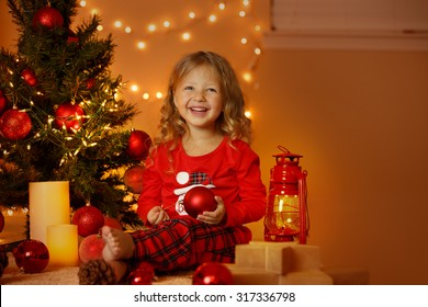 Happy cheerful little girl excited at Christmas Eve, sitting under decorated illuminated Christmas Tree. Greeting card or cover, horizontal with copy space.