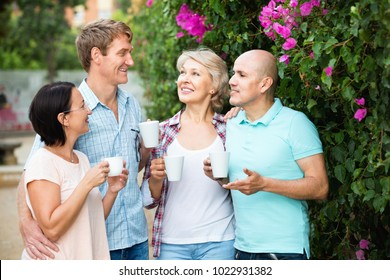 Happy cheerful  mature couples walking and drinking coffee on holiday