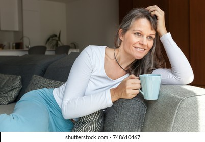 happy and cheerful middle aged woman drinking her morning coffee in her bright city apartment living room