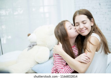 happy and cheerful mother with her  daughter in the living room at home