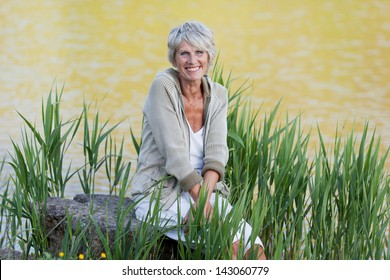Happy and cheerful old lady sitting near the lake and enjoying the views.