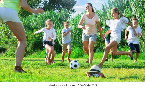 Happy cheerful  parents with children gaily spending time together playing with ball outdoors