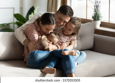 Happy cheerful parents having fun with cute children daughters cuddling playing on sofa together, mom and dad laughing embracing little kids daughters tickling enjoying family lifestyle games at home