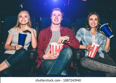 Happy and cheerful people are sitting and watching movie. They are excited. Blonde girl has a cup of cola. Guy holds a basket with popcorn. Brunette girl has all of it in her hands and smiling.