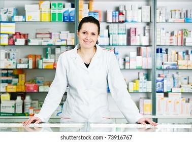 Happy cheerful pharmacist chemist woman standing in pharmacy drugstore