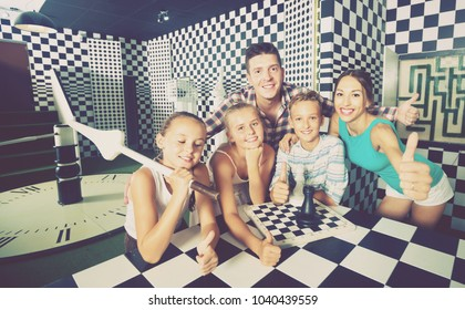 Happy cheerful positive  family of five is satisfied of visit together of lost chessroom.