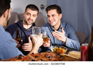 Happy cheerful positive male friends enjoying сonversation while drinking beer with pizza at home