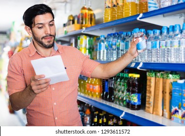 Happy cheerful positive  man is choosing water with help note list in supermarket.