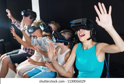 Happy cheerful positive  mother is impressed of VR with family in the room.