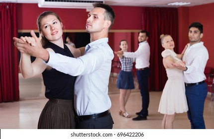 Happy cheerful positive people learning to dance waltz in dancing class