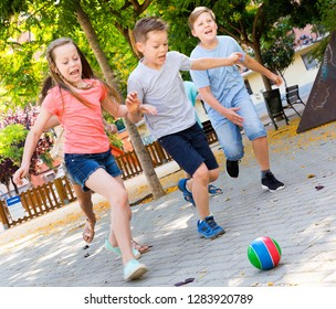Happy cheerful positive smiling children  playfully running after ball outdoors in park