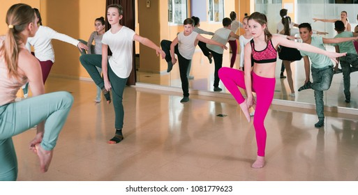 Happy cheerful positive smiling teenagers dancers practicing dance routine with female choreographer in modern studio
