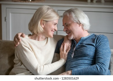 Happy cheerful senior retired couple sitting on sofa in cozy living room, loving husband embrace beloved wife, aged people chatting enjoying time together at home feeling comfort and positive emotions