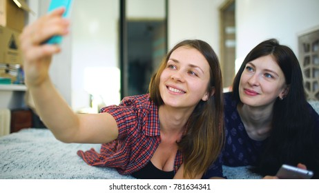 Happy cheerful sisters making selfie in morning and have fun on bed in bedroom at home