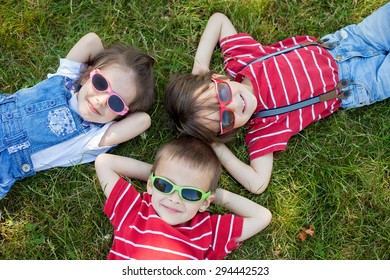 Happy cheerful smiling children, laying on a grass, wearing sunglasses, smiling at the camera, shot from above