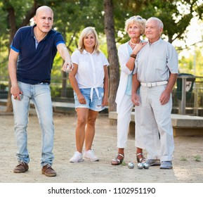 Happy cheerful  smiling family playing petanque in outdoor
