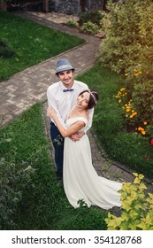 Happy cheerful smiling just married couple standing in park. Bride and groom hugging at sunset and looking in camera