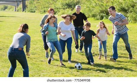 Happy cheerful  smiling people of different ages playing football on grass