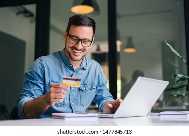 Happy cheerful smiling young adult man doing online shopping or e-shopping satisfied entrepreneur making online payment paying for service or goods self employed freelancer collecting fee