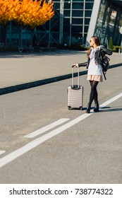 Happy cheerful traveler hipster woman standing with suitcases on the road over airport building in autumn time. Concept of travel, holidays, journey, trip.