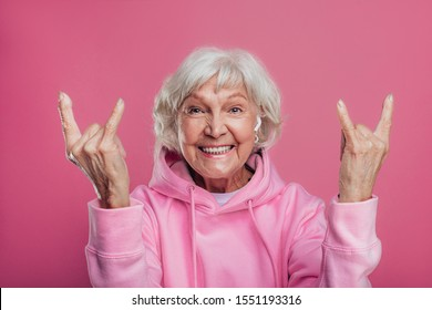 Happy cheerful and very emotional old woman show some fingers up in rock position. Smiling wide. Wear modern pink hoody. Stand alone. Isolated over pink background