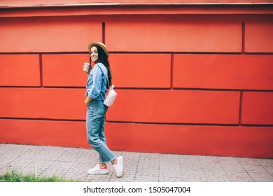 Happy cheerful woman with coffee cup walking at city street and smiling during leisure time for exploring world, positive smiling Caucasian tourist in trendy fashion outfit rejoicing outdoors