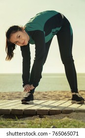 Happy cheerful  woman doing exercises on beach by ocean at daytime