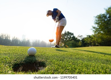 happy and cheerful of the woman golf player in winning putt a ball completed into the hole on the green
