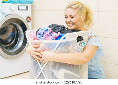 Happy cheerful woman holding big laundry basket full of colorful dirty clothes. Bathroom utensils concept.
